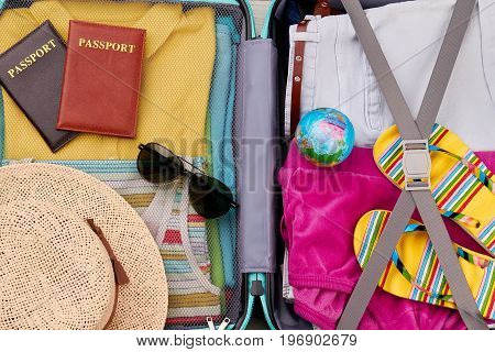 Close up of packed suitcase. Essential stuff for summer resort in traveler bag.