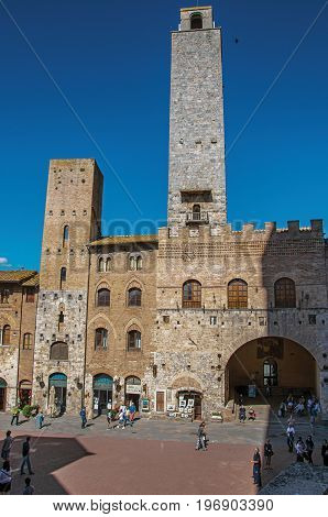 San Gimignano, Italy - May 13, 2013. View of square with people, old buildings and towers in San Gimignano. A medieval town famous for having several towers in its historical center. Tuscany region