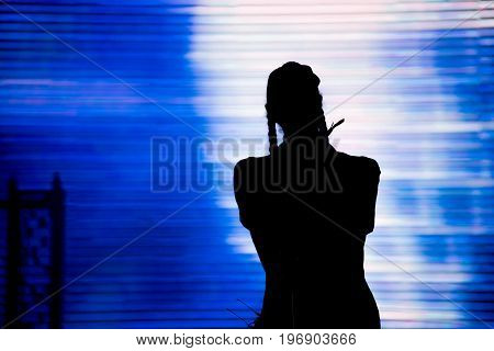 Silhouette of an artist singing live on the stage in the front of a colorful background