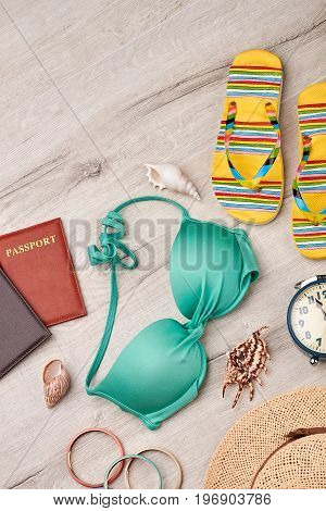 Women accessories for beach rest. Marine holiday setting, wooden background.