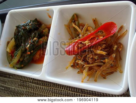 Appetizers of small dried fish with a slice of red pepper and lettuce leaves in kimchi on a small white tray Small dried fish or bolinao is very popular in the Philippines