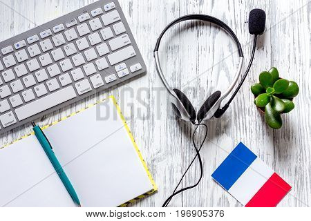 Learning languages online. Headphones and keyboard on wooden table background top view.