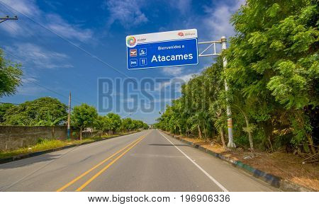 Esmeraldas, Ecuador - March 16, 2016: Paved road in the coast, with informative sign, surrounded with abundat vegetation in a sunny day in the Ecuadorian coasts.