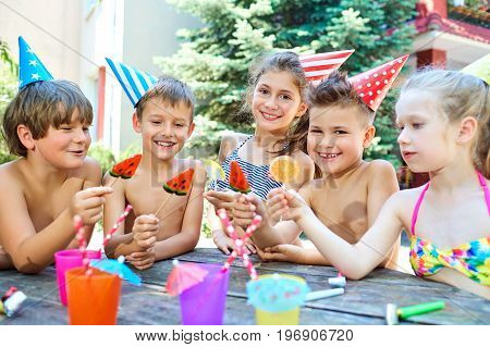 Birthday. Happy children in hats with colorful candy.