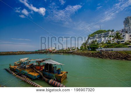 MANABI, ECUADOR - JUNE 4, 2012: Close up of a water pumping machine in a stagnant water with a at Same, Ecuador in a beautiful blue sky in a sunny day.