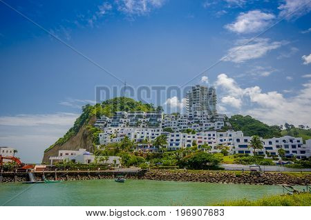Esmeraldas, Ecuador - March 16, 2016: Beautiful rocky beach with a buildings structure of hotels behind in a beautiful day in with sunny weather in a blue sky in Same, Ecuador.