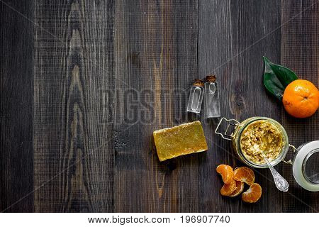 Making organic scrub. Scrub in glass jar, oranges, soap and oil on dark wooden background top view.