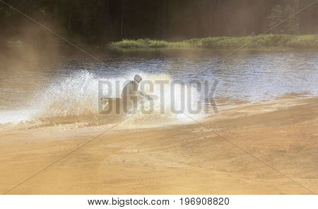 Man driving ATV quad through splashing water with high speed on a beach.