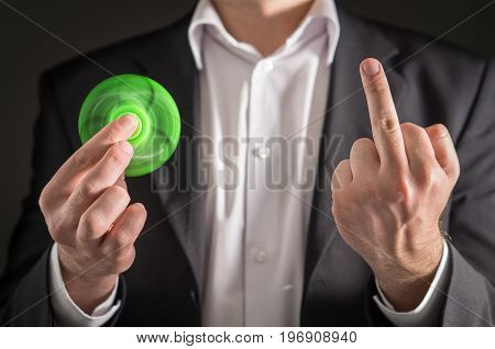 Business man holding a fidget spinner and showing middle finger. Businessman with attitude and a trendy kids anxiety relief toy. Funny, sarcastic and ironic behavior concept.