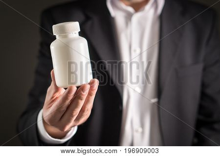 Pharmaceutical representative, consultant or head director or manager of medicine company with medicine bottle. Man in a suit holding pills or tablets in white container. Medical business concept.