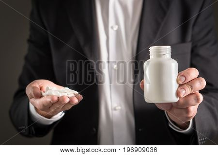 Pharmaceutical representative, consultant or head director or manager of medicine company with white tablets. Man in a suit holding pills and medicine bottle in hand. Medical business concept.