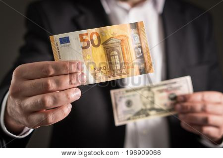 Dollar vs euro. Business man in suit holding 50 banknote and bill in both currency in hand. Exchange rate, world economy and financial concept.