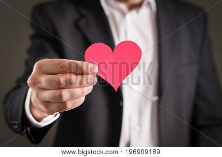 Man in a suit and a cardboard paper heart. Businessman or fiance with a love symbol. Proposal, wedding, dating or valentine's day concept.