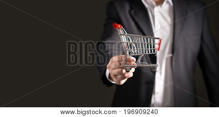 Grocery store chain management, retailing and daily consumer goods trade concept. Business man in a suit with a small miniature shopping cart. Copy and negative blank empty space.