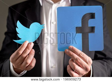 JYVASKYLA, FINLAND - JULY 23, 2017: Man in a suit holding printed carboard Twitter and Facebook logo. Both companys are known for their social media services and websites. Illustrative editorial.