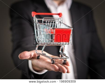 Grocery store chain management, retailing and daily consumer goods trade concept. Business man in a suit with a small miniature shopping cart.