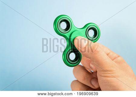Fidget spinner between fingers against blue background.