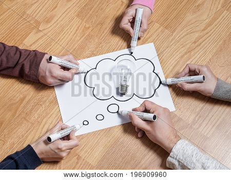 Thinking speech bubble balloon with light bulb. Brainstorming new ideas together for marketing plan or school project. Teamwork, synergy and education. Group of people drawing to same paper.