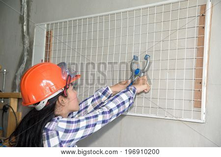 Young beautiful Asian woman holding and install white plastic mesh with pliers on the wall in shop.
