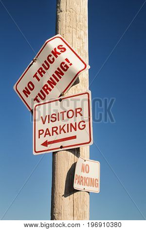 Parking and no trucks turning signs on wooden utility pole