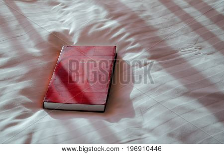 New Testament on hotel bed with light protruding into the room, with copy space. Red bible with beautiful lighting.