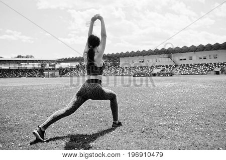 Portrait Of A Beautiful Woman In Sportswear Stretching Her Muscles In The Stadium. Black And White P