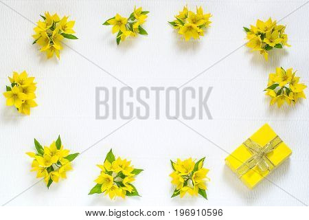 Festive flower arrangement. Flowers loosestrife (lysimachia) and gift in yellow packing on white textured background. Top view flat lay