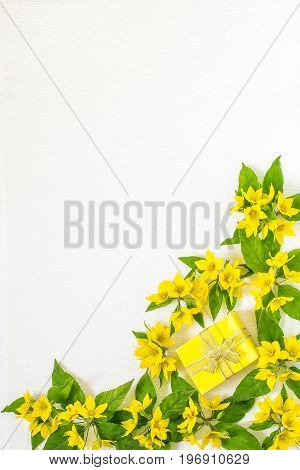 Festive flower arrangement. Flowers loosestrife (lysimachia) and gift in yellow packing on white textured background. Vertical top view flat lay