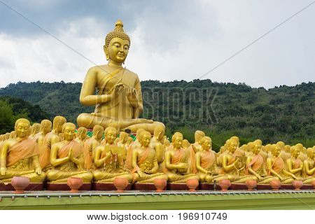 Big Golden Buddha Statue surrounding by small Buddha Statues at Buddha Makabucha Memorial park Nakornnayok Thailand. Two small buddha were taken as foreground. Copy space on the right.