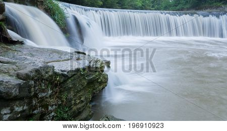 Beautiful waterfall in nature in switzerland in forest with stones