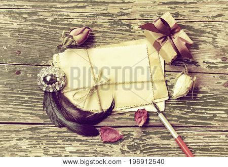 Vintage background with antique brooch pack of greeting cards tied with rope feathers and gift box on wooden table toned image