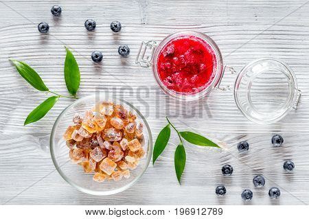 Raspberry jam in glass jar on grey wooden background top view.
