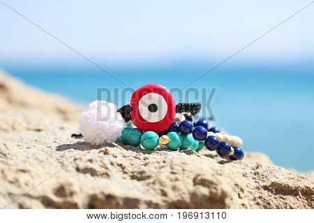 greek summer jewelry with evil eye and semi precious stones on the beach