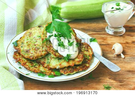 homemade fried fritters of zucchini with sour cream sauce herbs garlic towel on a wooden table