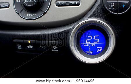 Digital controller display of air conditioner in car interior with twenty-five temperature climate adjustment. selective focus. Automotive part concept.