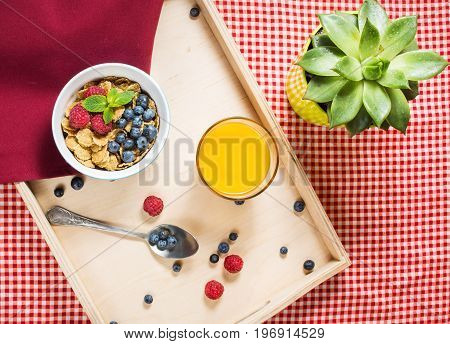 Multigrain wholewheat healthy cereals with fresh berry and a glass of juice for breakfast. Top view