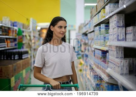 Beautiful young woman shopping in a grocery store supermarket