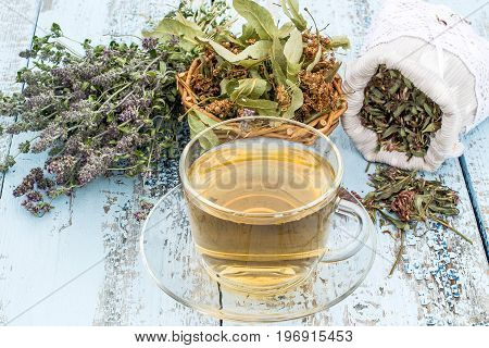 Various dried meadow herbs and herbal tea on light old wooden table. Dried medicinal plants in bag basket and in bundle. Preparing medicinal plants for phytotherapy and health promotion