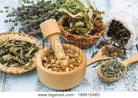 Various dried meadow herbs on light old wooden table. Dried medicinal plants in bag basket mortar and in bundle. Preparing medicinal plants for phytotherapy and health promotion