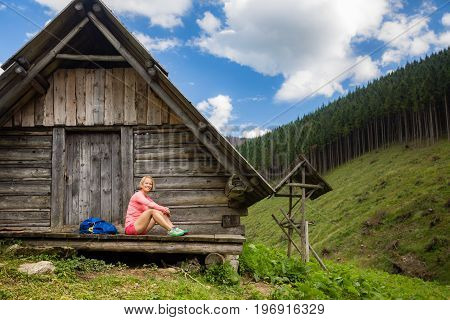 Young woman hiker camping and resting in beautiful Tatra mountains on hiking trip in shelter. Inspirational landscape in Poland. Active girl resting outdoors in summer nature.