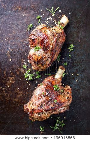 Two Barbecue Leg of Lamb as top view on old rusty metal sheet