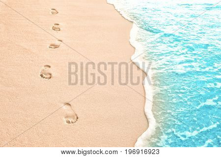 Human footprints on beach sand at resort in evening