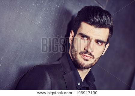 Closeup portrait of handsome young businessman looking away.