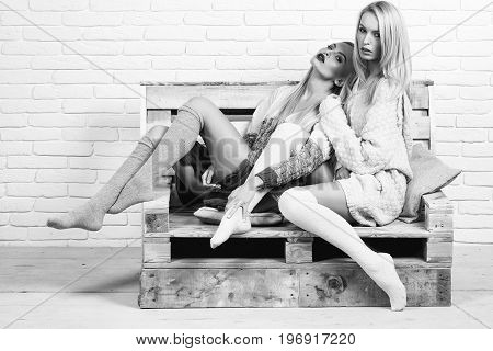 women with blond hair in home sweaters and socks sit on wooden pallet sofa on white brick wall black and white