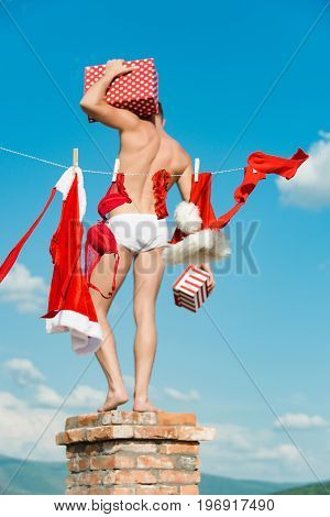 New year guy with muscular body on blue sky. Christmas man hold present box. Laundry and dry cleaning. Santa claus at clothes for drying on chimney. Xmas red costume on rope with pin.