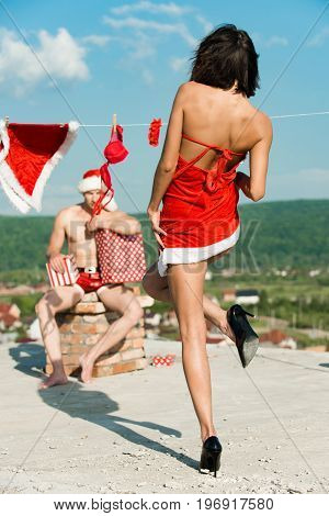 Xmas red costume on rope with pin. Laundry and dry cleaning. New year guy with muscular body on blue sky. Christmas man and woman family . Couple in love of man and girl hanging clothes for drying.