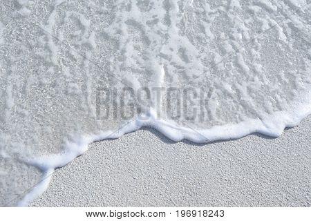 Warm sand and sea waves on beach at resort, closeup