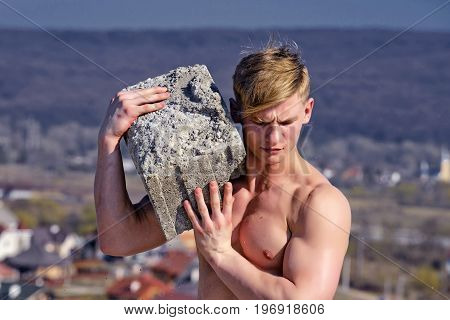 Adam hold bog stone. Sport and workout. Athletic bodybuilder as hercules. Gladiator or atlant. Man builder with muscular body.