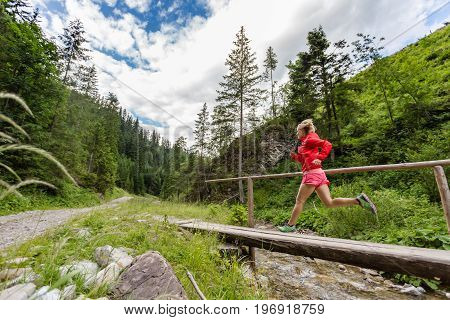 Young woman running in mountains on summer sunny day. Female trail runner crossing bridge on a mountain river. Sport and fitness concept outdoors in nature.