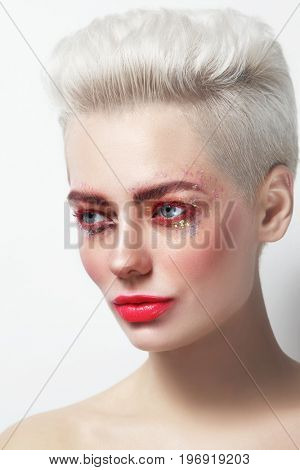 Young beautiful platinum blond glamorous woman with red mascara and glitters